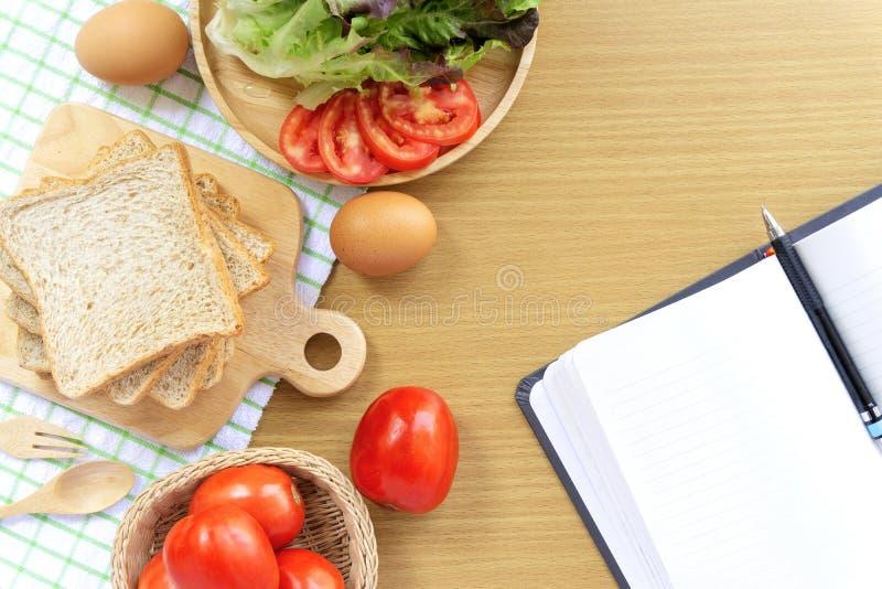 自制三明治早餐 全麦面包叠在木制切板上 笔记本、笔、番茄和生菜 图库摄影