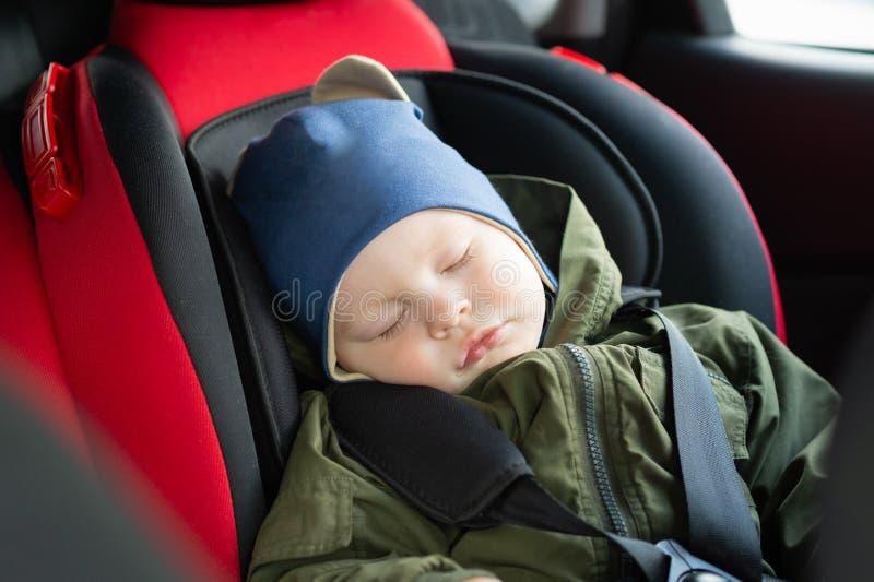 睡在现代汽车座椅上的白人可爱男婴 道路上的儿童旅行安全 安全的旅行方式 免版税库存图片