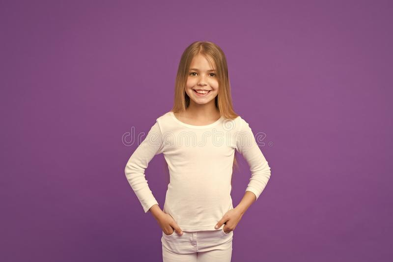 Παιδί που φορά λευκό πουλόβερ και τζιν, ιδέα της μόδας για νέους Κορίτσι με μακριά λαμπερά ξανθά μαλλιά Υπέροχο παιδί με μεγάλο στοκ εικόνα