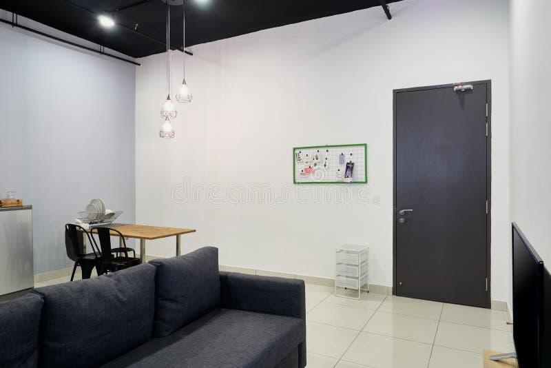 Un divano nero in un piccolo soggiorno di un appartamento in studio Un piccolo tavolo da pranzo in sottofondo Un muro bianco con  immagine stock