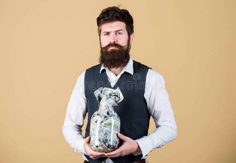 Przeliczanie waluty krajowej na dolar Biznesmen zatrzymuje dolary w szklanym słoiku Brodaty mężczyzna trzymający Amerykanina zdjęcia stock