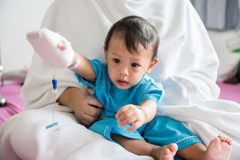 Kinderziekte Little Baby dat de intraveneuze tube aan de hand van de patiënt in het ziekenhuisbed vastmaakt Baby ziek en huilend  royalty-vrije stock afbeelding