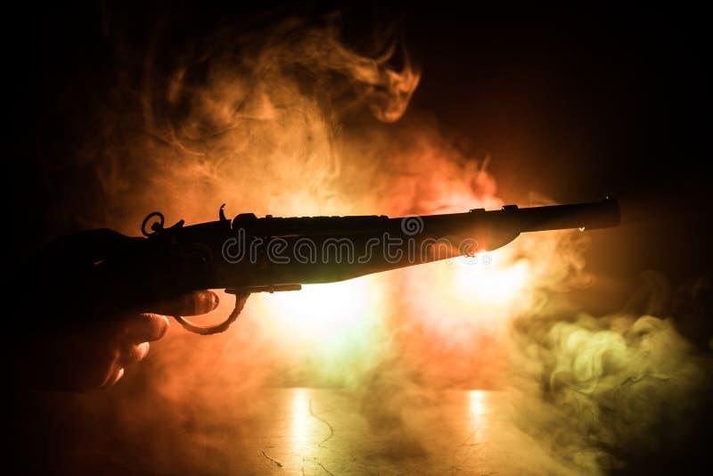 Мужчина держит пистолет на черном фоне с дымовыми задними огнями Силуэт оружия в руках Концепция преступности стоковое изображение rf
