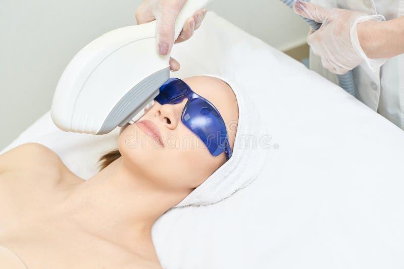 Rimozione laser dei capelli facciali Dispositivo IP di cosmetologia Corpo femminile in clinica Ragazza di bellezza medica Strumen fotografie stock libere da diritti
