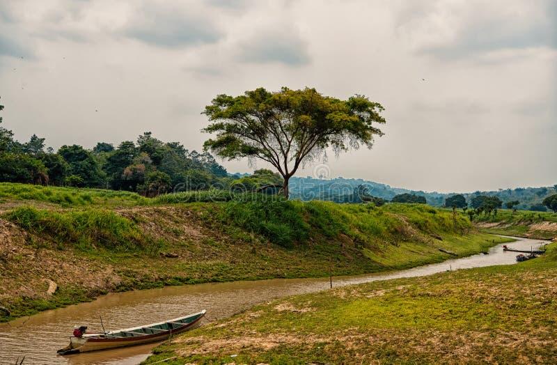 Шлюпка на Амазонке в boca de валерии, Бразилии Подача Амазонкы на тропический ландшафт на облачном небе Бразилии r стоковые изображения