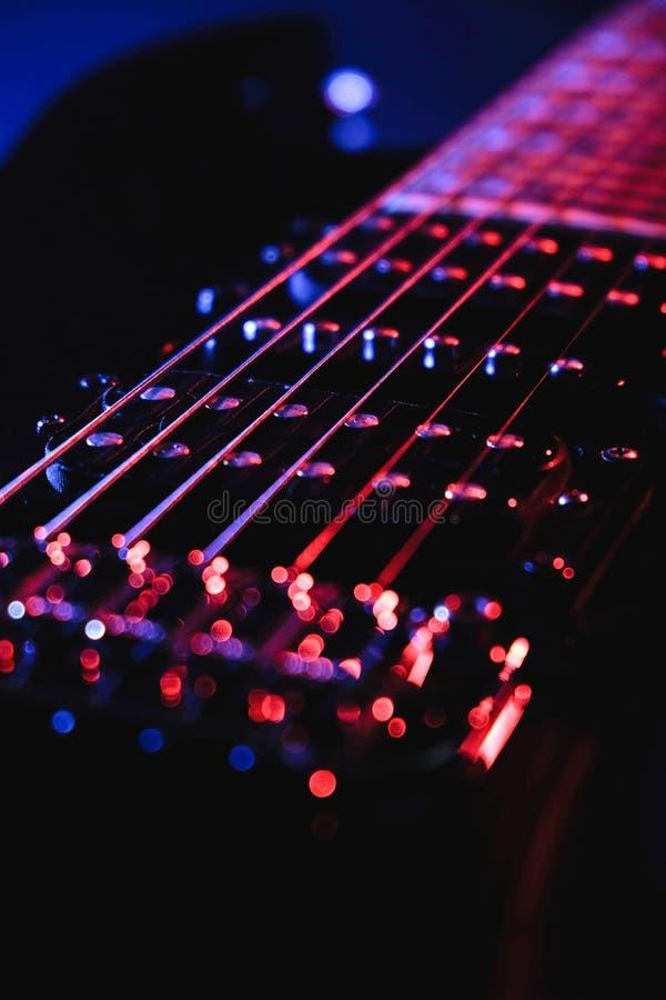 Sluiting van een bultrug Detail van de zes-koord elektrische gitaar, zachte selectieve nadruk Met kleurrijk blauw en paars illumi stock afbeeldingen