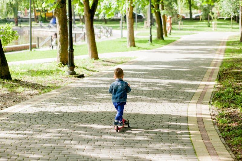 城市公园小男孩骑摩托车 户外运动 快乐的孩子玩他的滑板车 孩子学会骑 免版税库存图片