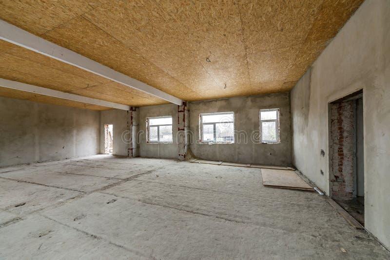 在重建下的未完成的公寓或房子大顶楼室 胶合板天花板,涂灰泥的墙壁,窗口开头,水泥地板 库存照片