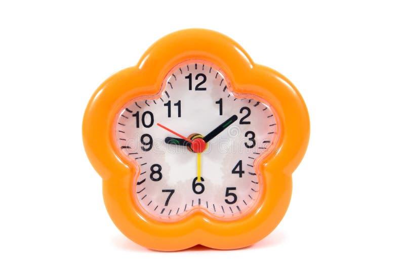 在白色背景隔绝的橙色闹钟 r 免版税库存照片