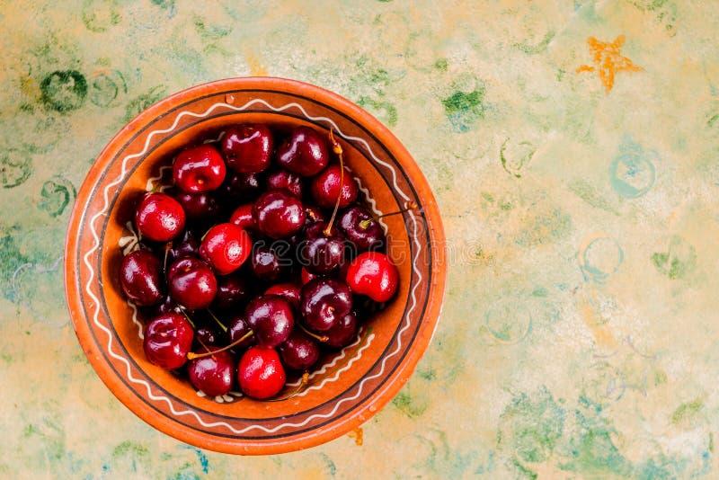 Шар со свежими вишнями на деревянной голубой предпосылке Зрелые сладкие вишни E r стоковое фото rf