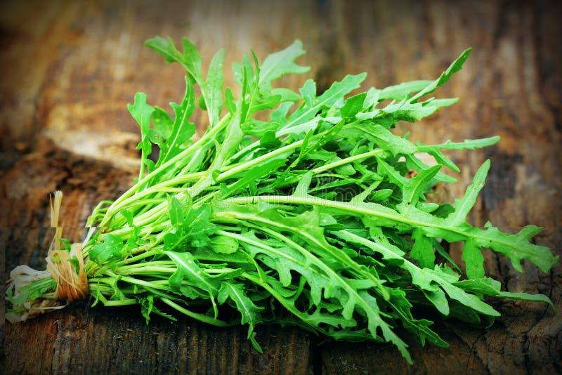 Νωπά πράσινα φύλλα αρούγας σε ξύλινο ρουστικό φόντο Σαλάτα με ρουκέτα ή ρουκόλα, υγιεινό φαγητό, διατροφή Έννοια της διατροφής στοκ φωτογραφία με δικαίωμα ελεύθερης χρήσης