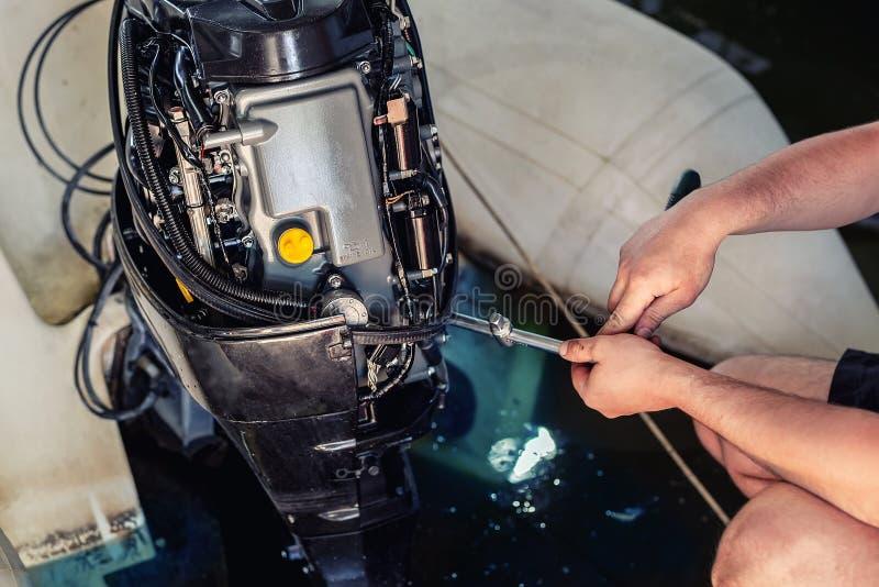 riparazione meccanica del motore gonfiabile a motoscafo nel garage Servizio stagionale e manutenzione del motore navale Motore de fotografie stock libere da diritti