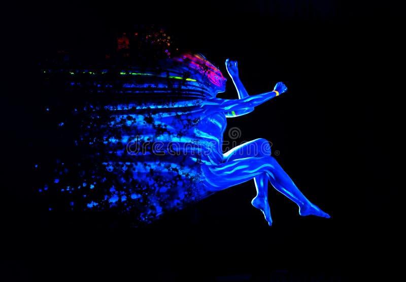 Arte corporal ultravioleta brillante en el cuerpo de una joven mujer Dispersar a la chica con fondo negro Concepto creativo de ar imágenes de archivo libres de regalías