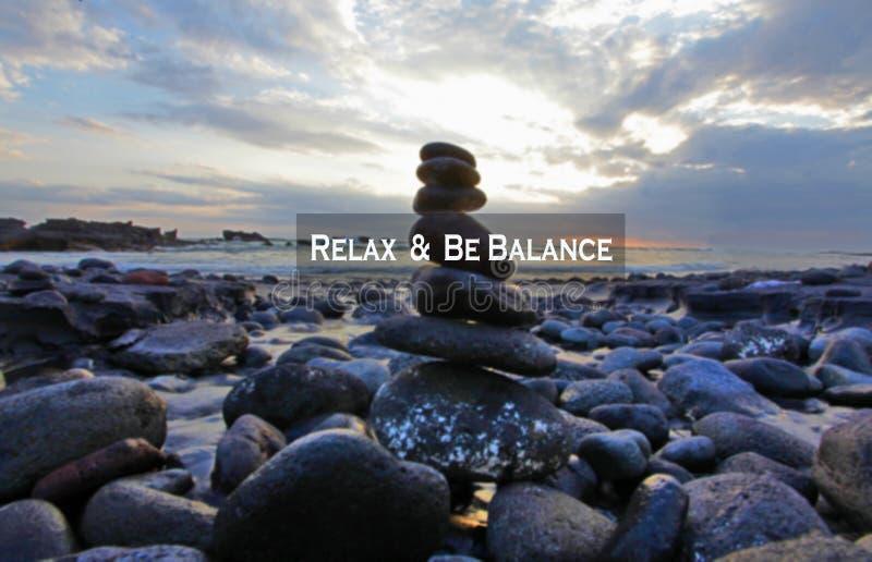 Proposta de saldo Citação motivacional inspiradora - Relaxe e seja equilibrado Com pedras do mar equilibram formação na praia roc imagem de stock royalty free