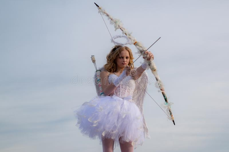 云天背景上可爱的青少年丘比特 可爱可爱的青春 有弓箭的可爱女孩丘比特 库存照片