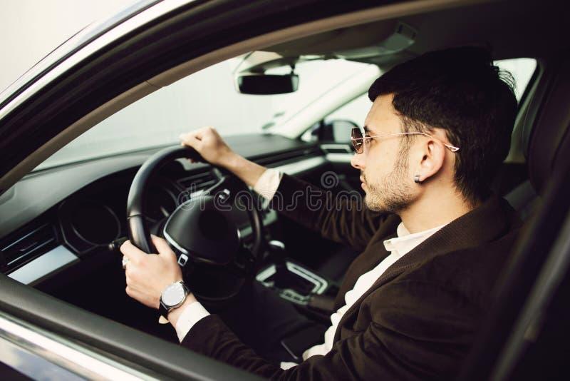 穿着西装和黑色眼镜的年轻商人开车 布西内斯 新车试驾 免版税库存照片