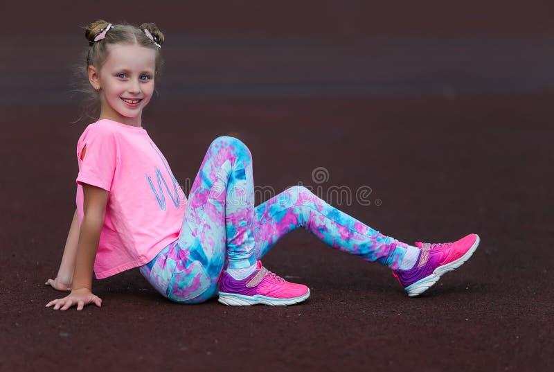 Fitness-kleines Mädchen ruhen nach Übungen im Stadion Sportmädchen im Stadion Fitnessmädchen mit Sportfigur in lizenzfreie stockbilder