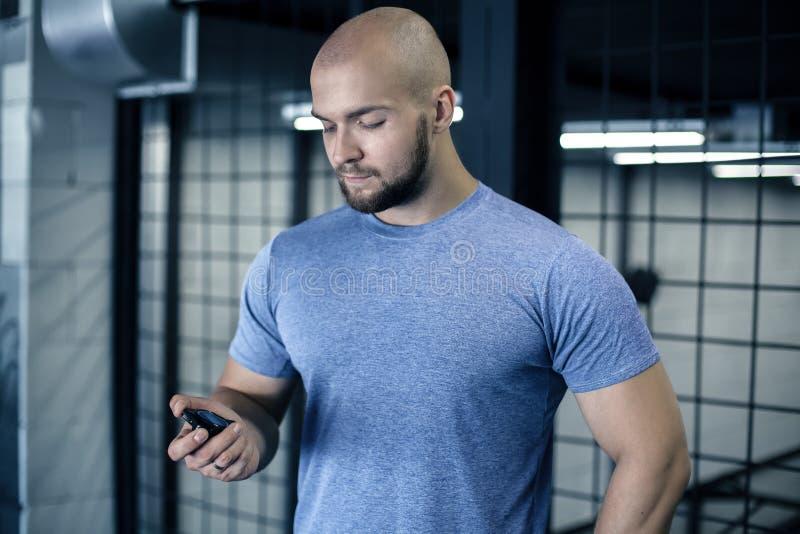 严肃的体育教练的画象有一个秃头的 看看秒表 锻炼是成功的 穿戴在体育制服 免版税图库摄影