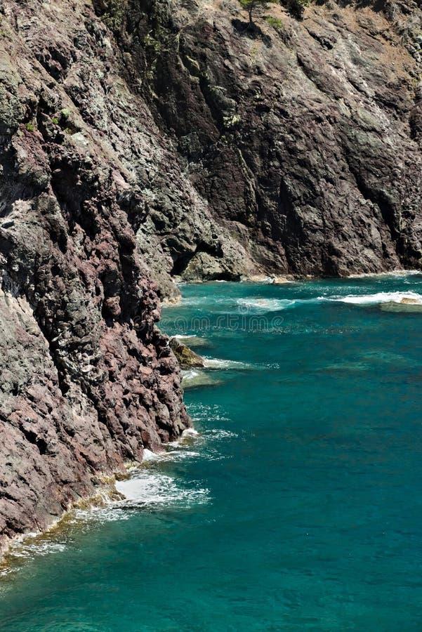 Havsvågor bryter på vaggar av det Ligurian berget Nära Cinque Terre en seascape med det blåa havet och mörkt - rött vaggar by fotografering för bildbyråer