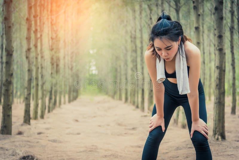 疲倦从跑步的亚裔秀丽妇女在森林毛巾和汗水元素 体育和健康概念 跑步和连续概念 免版税库存图片