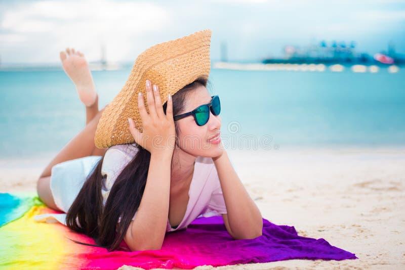偶然的亚裔说谎在热带海滩的妇女和草帽有海背景 放松和生活方式概念 假日和假期 库存照片