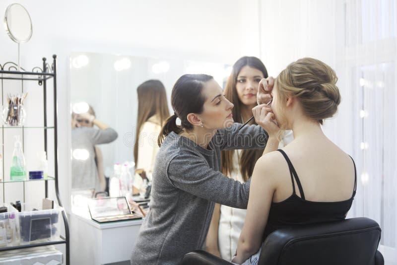 化妆老师和她的女学生 在美容学校补习 在她的工作室里画画 库存图片