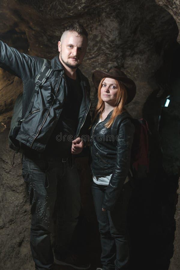 Молодые пары исследуя огромную пещеру Путешественники приключения одели ковбойскую шляпу и рюкзак, кожаную куртку весьма каникулы стоковое фото