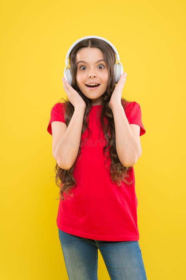 Stellen Sie den Ton gegenüber Entzückendes kleines Mädchen, das auf Tonspur auf gelbem Hintergrund hört Nettes kleines Kindertrag lizenzfreie stockfotos
