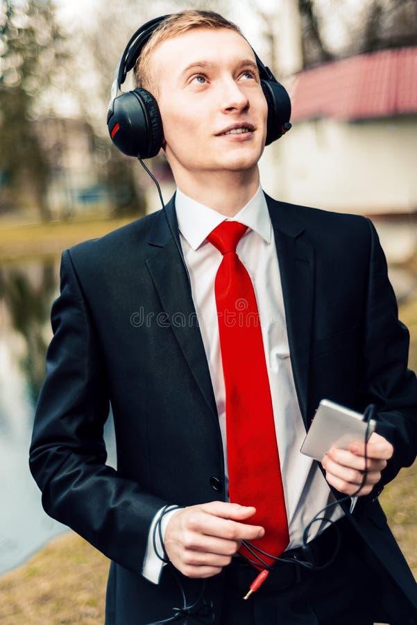 Jonge zakenman in hoofdtelefoons de kerel luistert aan muziek op de aard in het park een mens in een zwart kostuum en een rode ba stock foto