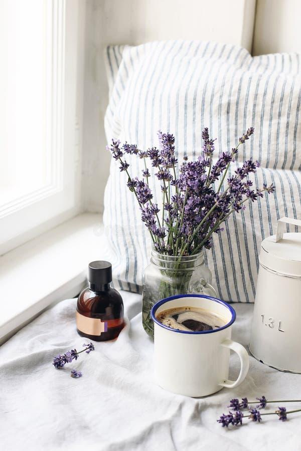 Французский натюрморт лета Чашка кофе, букет цветков лаванды, бутылка масла сути на windowsill Введенное в моду женственное стоковые фото