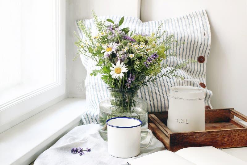 Sommerstilllebenszene Emailbecher, Blumenstrauß der wilden Blumen und Leinenkissen Weibliches angeredetes Foto der Weinlese, rust lizenzfreies stockfoto