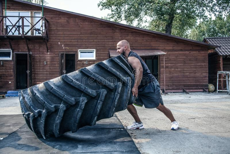 轮胎轻碰锻炼 秃头运动员参与与重的轮胎的锻炼在街道健身房 举的概念,锻炼训练 免版税图库摄影