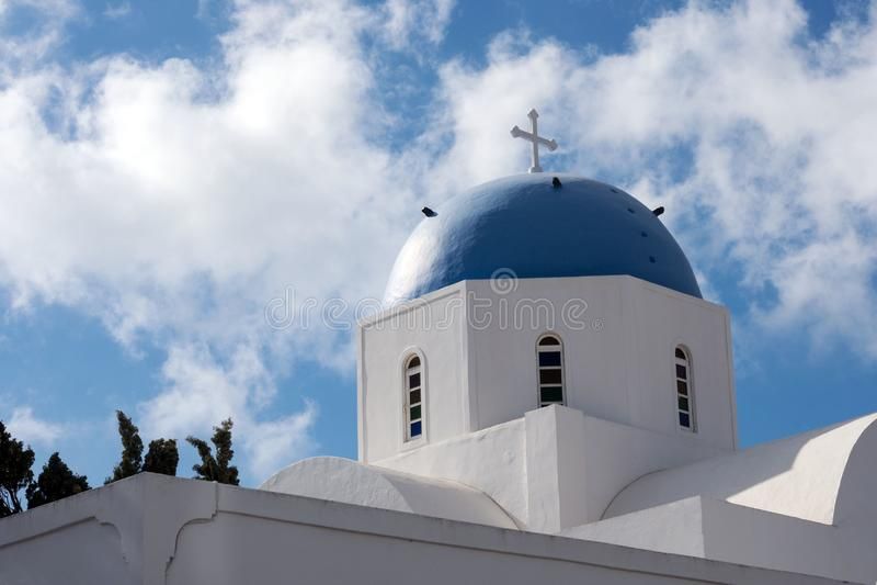 圣托里尼,希腊美丽的海岛  有一个蓝色圆顶的白色教会在Oia村庄在圣托里尼海岛上的  希腊journ 库存照片