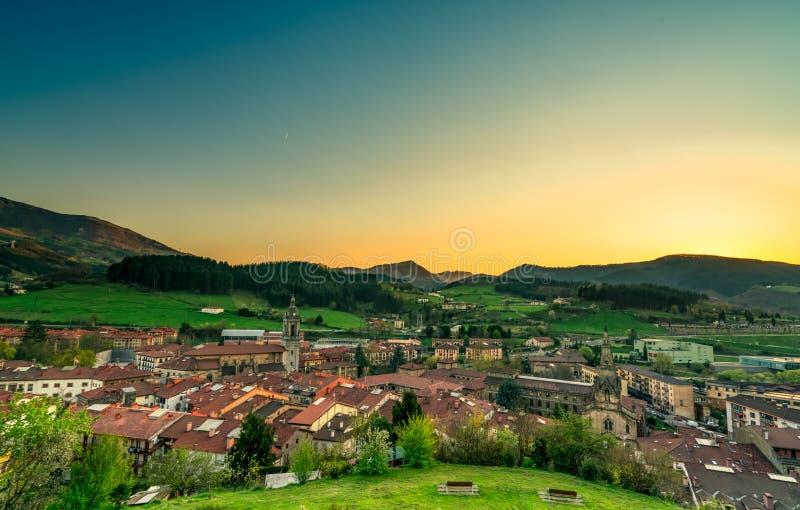 山谷中的城市 黄蓝晨间的阳光,在山上 欧洲春季 绿草 免版税库存照片
