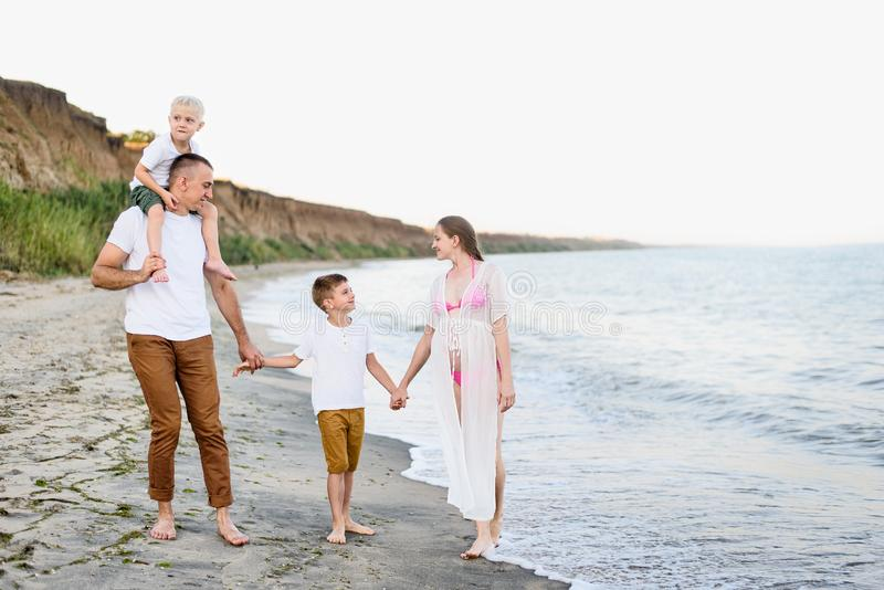 四口人在海边散步 父母和两个儿子 幸福的家庭 免版税库存图片