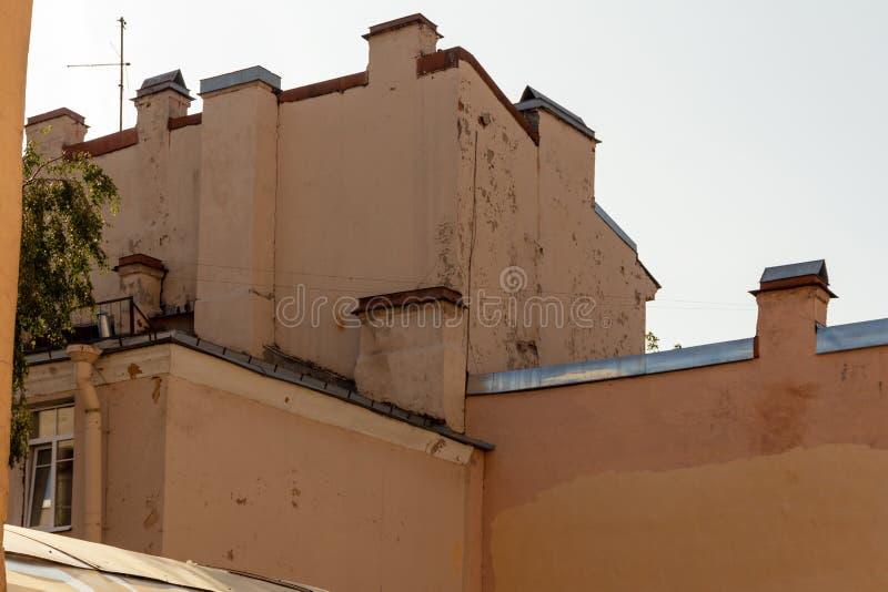 Vista dal basso sulle vecchie pareti di costruzione un giorno di estate Tetto di prospettiva con i camini e le antenne La urbana  immagine stock