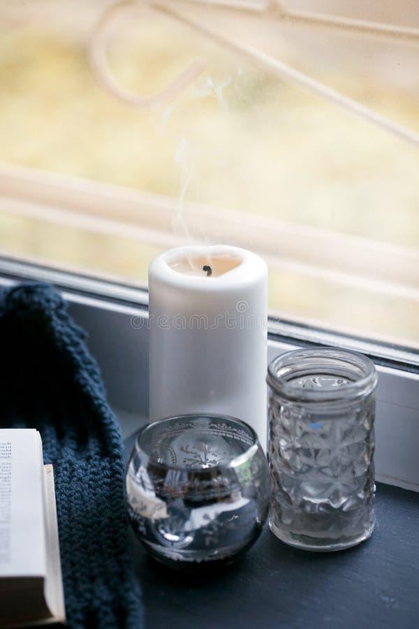 北欧客厅静物画细节  蜡烛和芳香棍子在窗台 在斯堪的纳维亚内部的舒适冬天场面 免版税库存图片