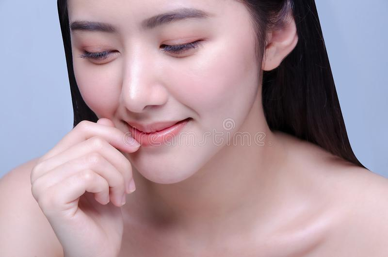 嘴唇保护 美丽的年轻亚裔妇女健康嘴唇特写镜头  接触她与光滑的女性模型豪华的嘴完善 免版税库存图片