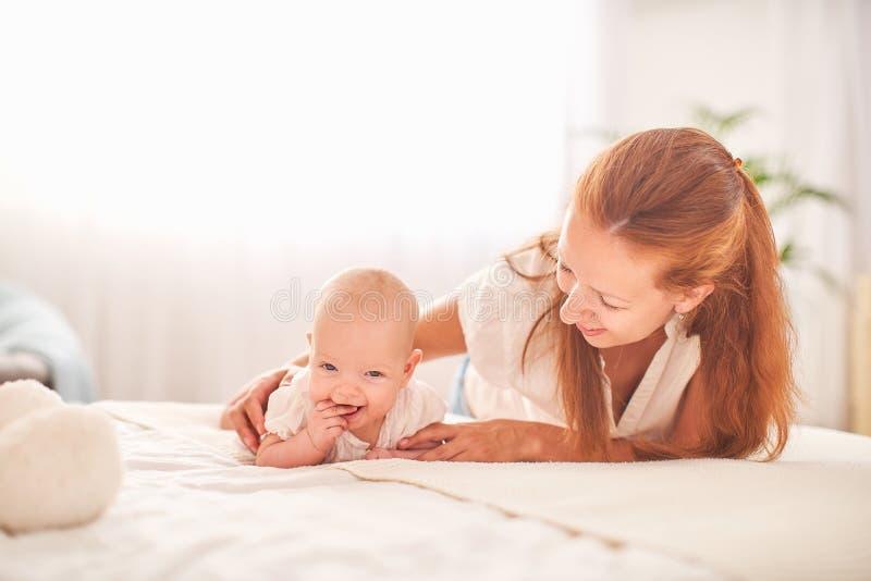 Bebé de la gimnasia mujer que hace ejercicios con el bebé para su desarrollo dé masajes a un pequeño bebé recién nacido foto de archivo libre de regalías