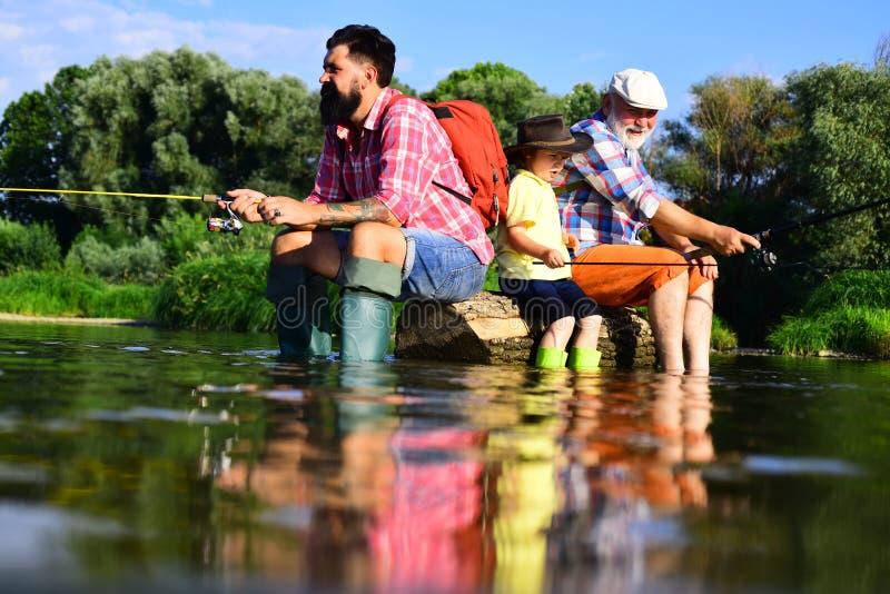 Familjutvecklings- och folkbegrepp Gammelfarfar och stor-sonson Fader som undervisar hans son som fiskar mot sikt royaltyfri bild