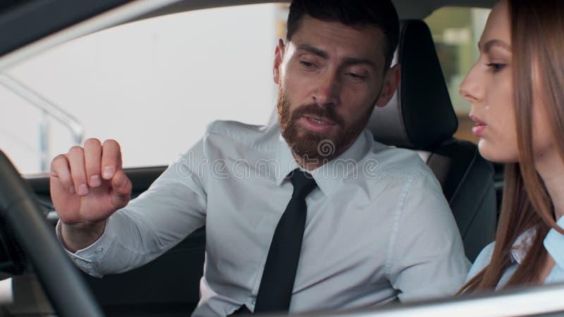 O vendedor mostra as características do carro do cliente O carro é novo O vendedor faz o melhor para vender este foto de stock