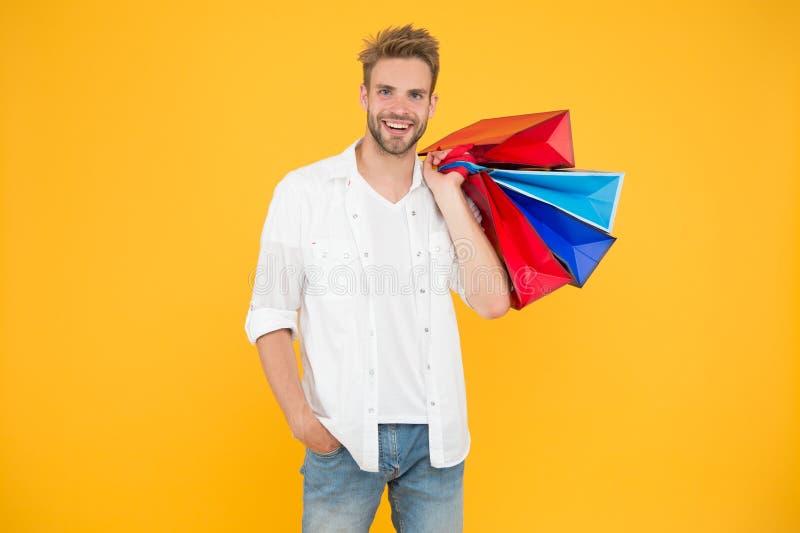 L'acquisto lo incita a ritenere meglio Uomo bello che sorride con i sacchetti della spesa su fondo giallo Tenuta felice del clien fotografie stock libere da diritti
