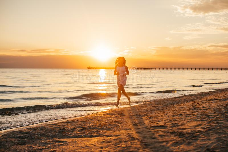 Kontur av den unga slanka härliga kvinnan på solnedgångstranden Flickan kör i en vit klänning Begrepp för sen sommar arkivfoto