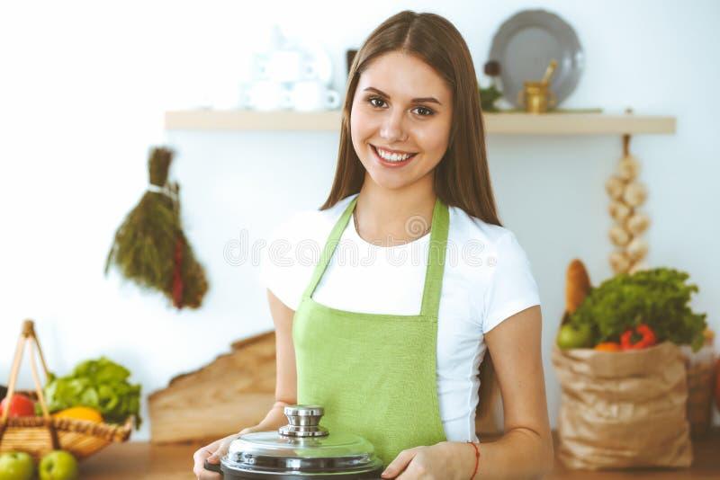 Молодая счастливая женщина готовит суп на кухне. Здоровое питание, обрРстоковая фотография