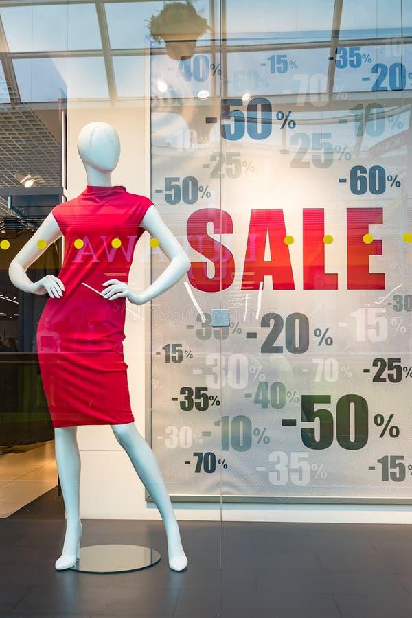 Säsongförsäljning, svarta fredag och shoppabegrepp Skyltdockor för en kvinna i röd kläder på i lager shoppar fönstret Sale tecken arkivbild