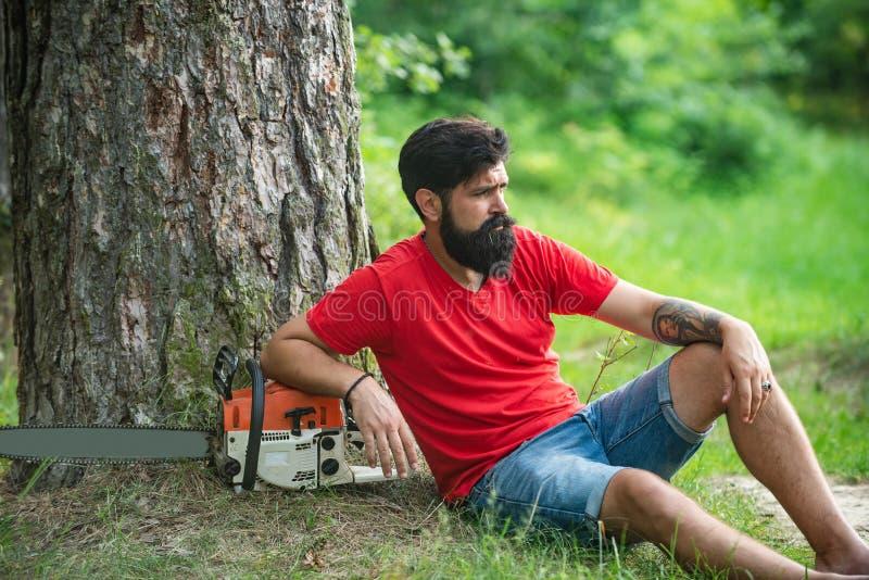 Un giovane con un'ascia vicino al bosco di Lumberjack con una motosega in mano Chainsaw La deforestazione è una delle cause princ fotografia stock libera da diritti