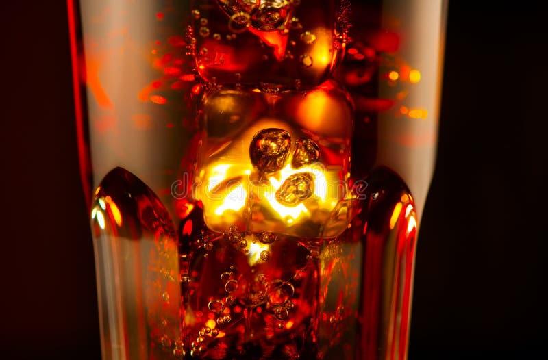 Fizzy Cola met ijskubusachtergrond Cacke drink met ijs, bubbels in een glas Soda closeup over zwarte achtergrond stock afbeelding