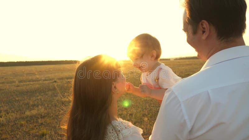 Pap en moeder spelen met een kleine dochter in haar armen bij zonsondergang familie loopt bij zonsondergang met een kind vader sp royalty-vrije stock afbeelding