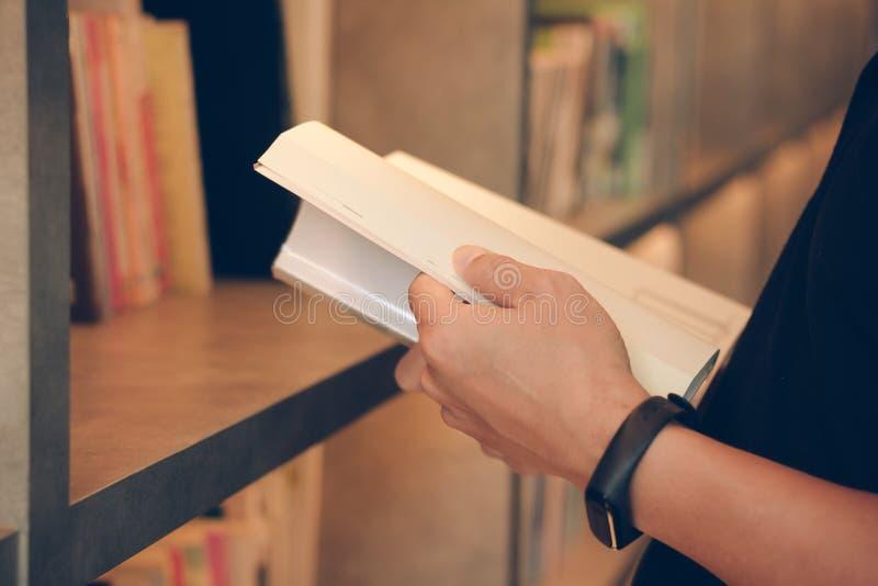 Młody człowiek czyta książkę w bibliotece, zamknij się Student na studiach z książki, wiedza w koncepcji uniwersyteckiej Badanie  obraz royalty free