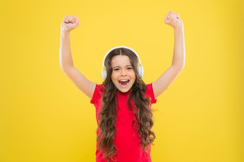 Hela musikvärlden i hennes öron Vanliga låtar Barn kan spela musik i hörlurar En liten flicka som gillar favorit royaltyfri bild